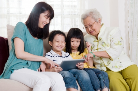 happy asian family: Asian three generations family having fun with tablet computer