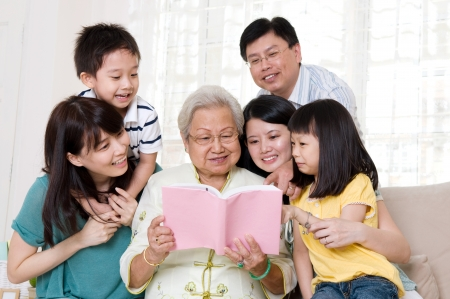 Asian family reading book at home photo