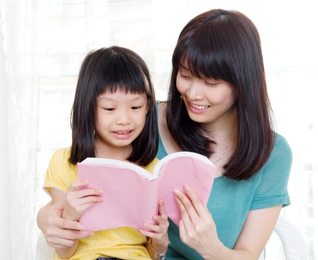 Asian mother and daughter reading a book photo