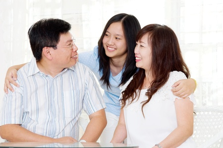 asian middle aged couple and their daughter photo