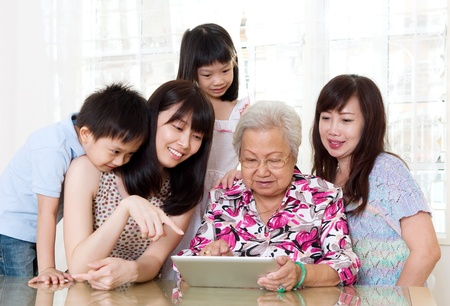 Asian senior woman learns to use tablet computer photo