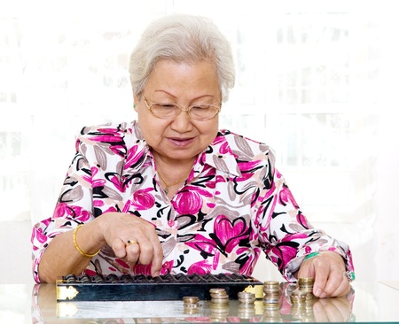 abaco: Mujer mayor asiática que usa el ábaco para contar monedas
