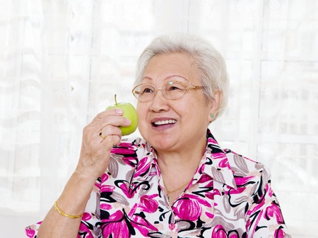 Asian senior woman eating an apple
