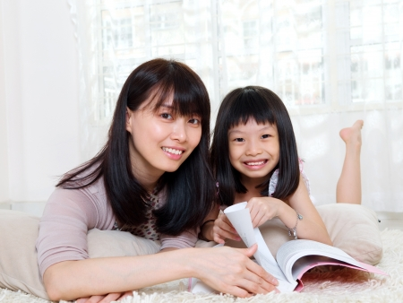 Asian woman and daughter lying on the floor and reading photo