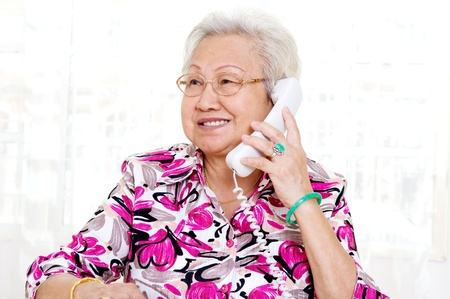 Asian senior woman in her 70s talking on the phone photo