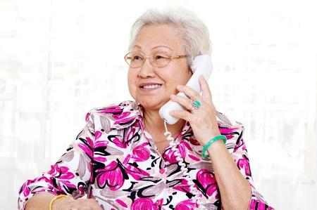 ecoute active: Senior femme asiatique de 70 ans en parlant au t�l�phone