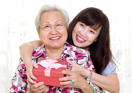 Asian senior woman receiving gift from daughter