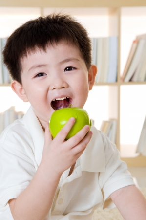 cute asian boy eating apple photo