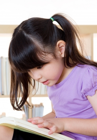 intelligently: Little girl reading a book Stock Photo