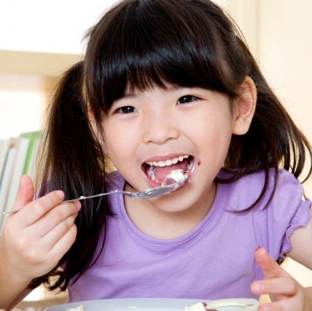 hungry kid: Asian girl eating with spoon Stock Photo