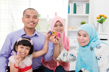 arab teen: Muslim family holding alphabet letters of  HOME  Stock Photo