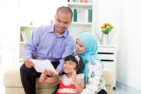 malaysian: muslim family using tablet computer