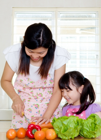 teaching children: Asian mother and daughter in the kitchen Stock Photo