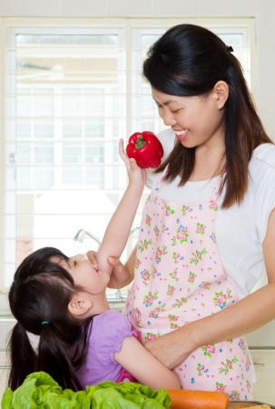 little asian girl helping mom in the kitchen photo