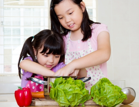 japanese cooking: Little asian girls cooking Stock Photo