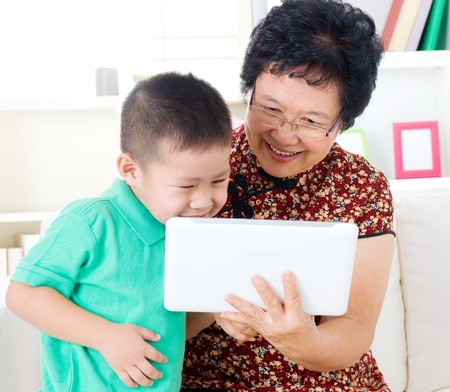 asian elderly: Asian senior woman and grandson using tablet computer Stock Photo