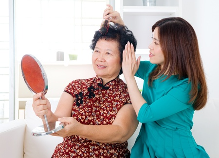 Asian woman helping mom to comb her hair photo