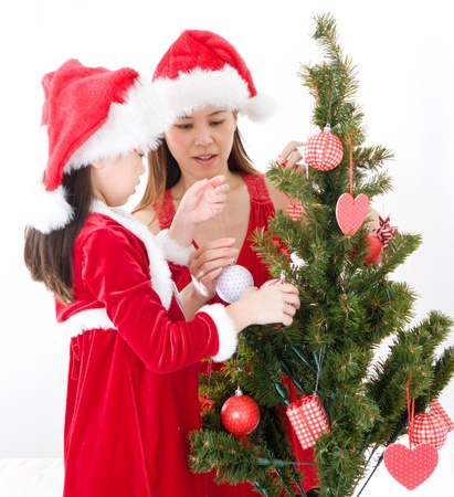 Asian mother and daughter decorating christmas tree photo