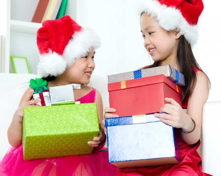Asian kids carrying Christmas present