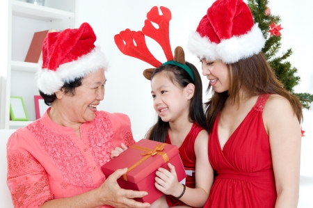 Lovely asian girl presenting Christmas gift to grandmother photo