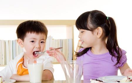 sharing food: Asian girl feeding her brother