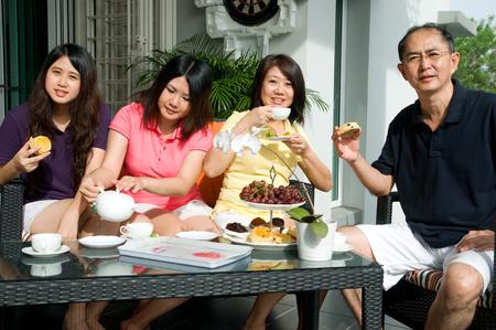 familia comiendo: Familia asiática disfrutando de la hora del té