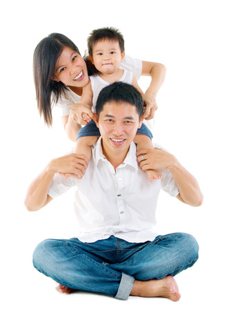 thai boy: Parents having piggyback fun with their lovely son  Stock Photo