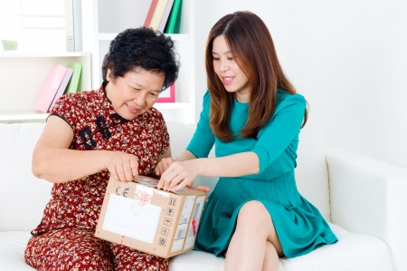 Asian senior woman and daughter opening a courier parcel photo