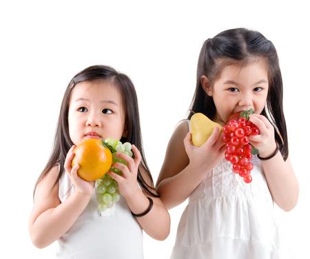 eating fruits: estilo de vida saludable concepto muchachas asi�ticas comer frutas Foto de archivo