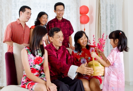 Mignonne petite fille donnant panier-cadeau à un grand-parent sur le nouvel an chinois Banque d'images - 24384346