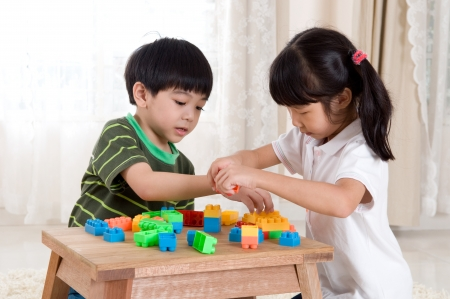 boys toys: Asian kids piling up building blocks Stock Photo