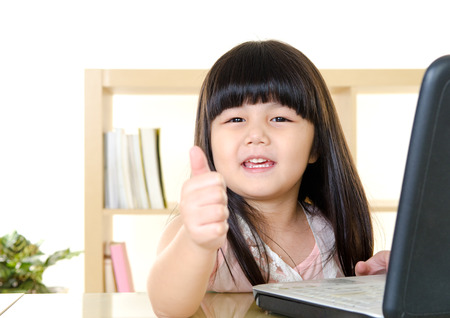 chubby girl: Cute asian girl using laptop and thumbs up Stock Photo