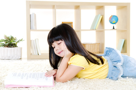 Cute girl lying on the floor and reading