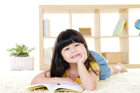 intelligently: Cute little girl reading Stock Photo
