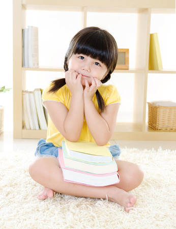 intelligently: Cute Asian girl sitting on the floor having a thought