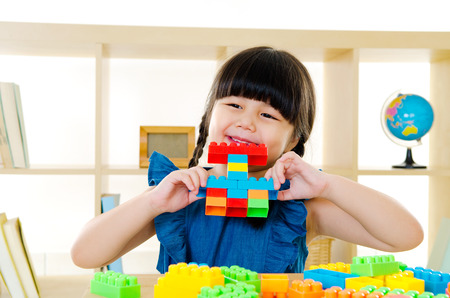 chubby girl: Asian kid piling up building blocks