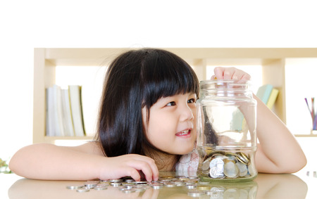 Little girl putting coins into the glass bottle  money saving concept  Stock Photo