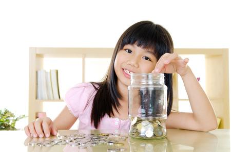 contando dinero: Muchacha asi�tica que pone monedas en el ahorro de dinero y concepto botella de vidrio Foto de archivo