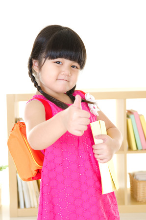 Asian elementary student with school bag raised her thumb