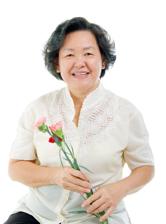 Asian senior woman holding carnation flower isolated on white Фото со стока