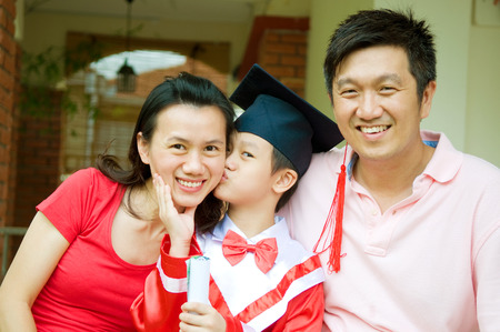 Asian kid giving an appreciation kiss to his mother on kinder graduation day Stock Photo