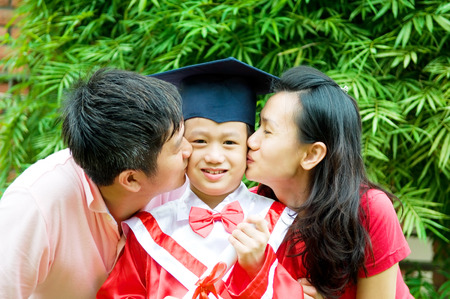 Asian parent kiss their son on his kinder graduation day  photo
