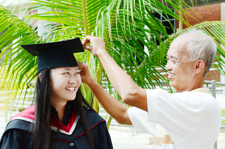 Father adjusting mortarboard for daughter on her university graduation day photo