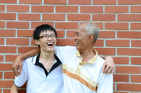 adult offspring: Asian father and son laugh happily Stock Photo