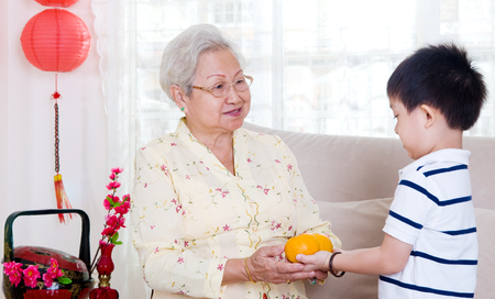 Asian boy giving mandarin oranges to his grandmother photo