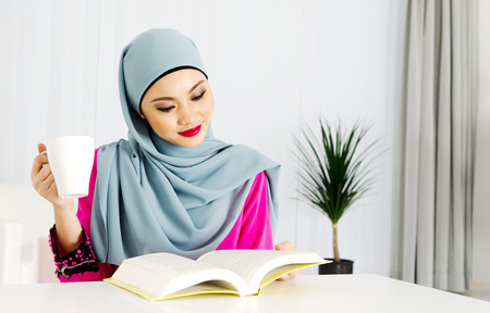 Muslim woman reading and having a cup of tea at home photo