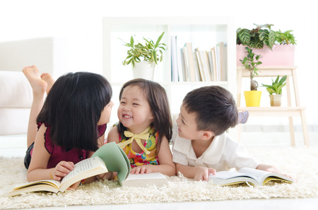 family at home: Asian kids lying on the floor
