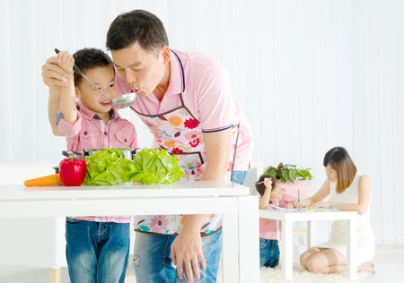 Asian father and elder son are cooking in the kitchen while mother is teaching younger son doing schoolwork.