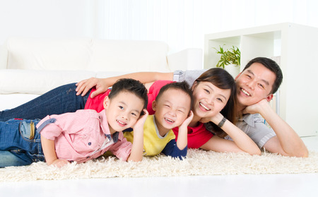 Asian family lying on the floor and smiling