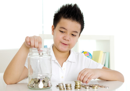 Asian boy putting coins into the glass bottle. money saving concept. Фото со стока